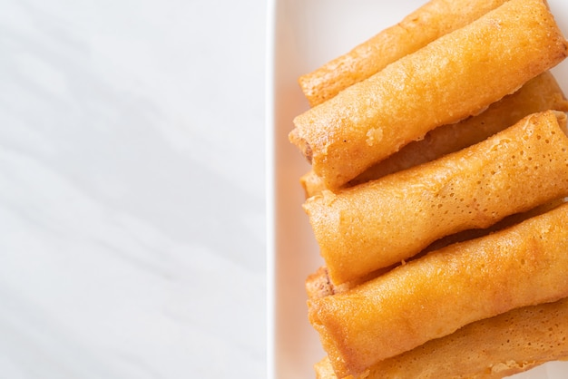 Deep fried spring roll with sauce on white plate