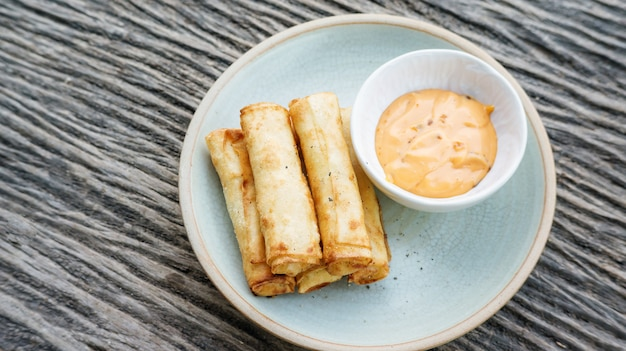 Deep fried spring roll on a wooden table.