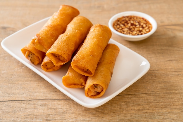 Deep fried spring rolls with sauce on white plate
