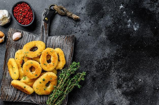 Deep fried squid calamari rings breaded on a cutting board