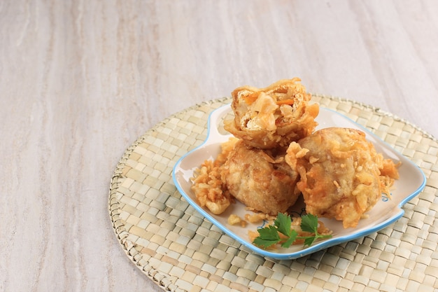 みじん切り野菜またはタフイシ(gehu pedas)を添えた白い豆腐の揚げ物、インドネシアの伝統的な人気スナック、テキスト用のコピースペース付きの茶色で分離