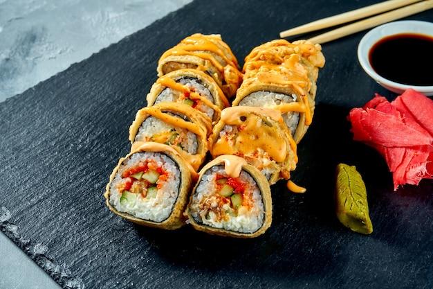Жареные во фритюре суши-роллы с угрем и огурцом в темпуре на черной грифельной доске. выборочный фокус