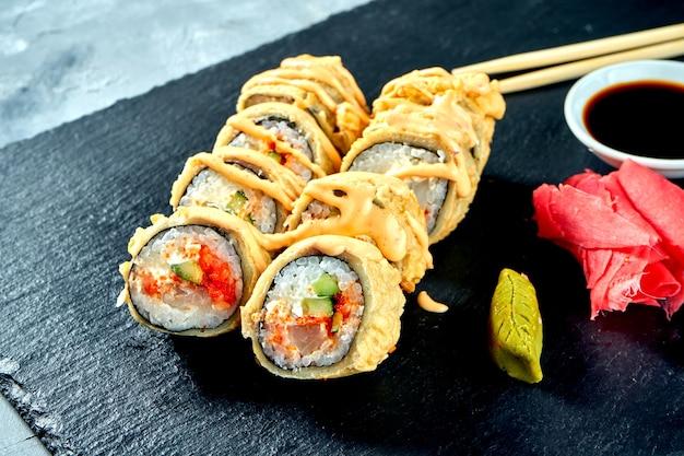 Жареные во фритюре суши-роллы с окунем и огурцом в темпуре на черной грифельной доске. выборочный фокус выборочный фокус