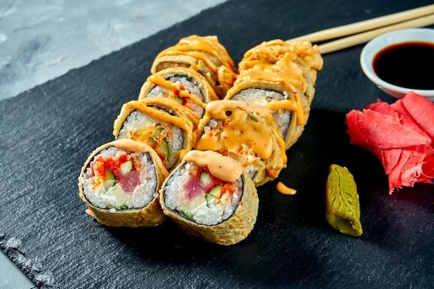 Жареные во фритюре суши-роллы с тунцом и огурцом в темпуре на черной грифельной доске. выборочный фокус выборочный фокус