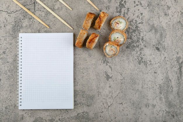 Deep-fried sushi with chopsticks and notebook on a stone background .