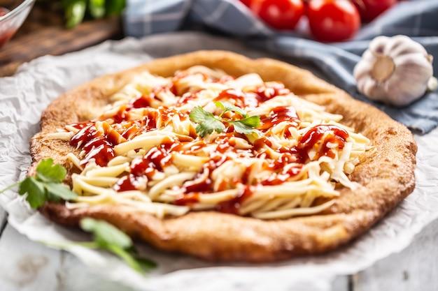 Жареные во фритюре вкусные венгерские сырные ланго с кетчупом, зеленью и чесноком.