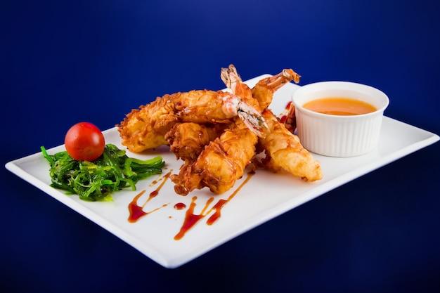 반죽에 튀긴 타이거 새우를 탕수육 소스, 김, 체리 토마토를 직사각형 접시에 곁들여 제공합니다.