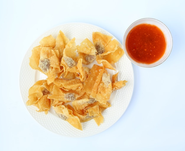 Deep fried wonton in white plate serve with sweet sauce on white background