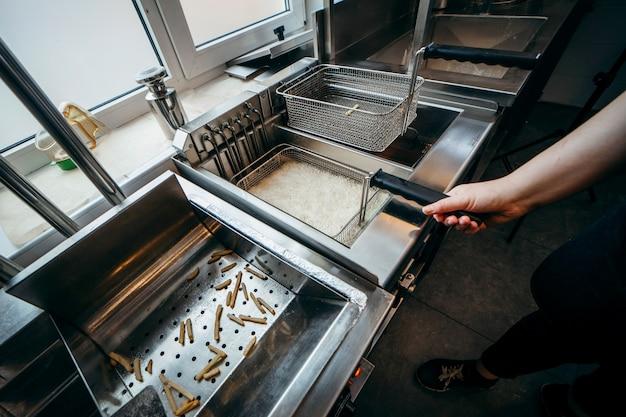 Deep fryer for potatoes in kitchen