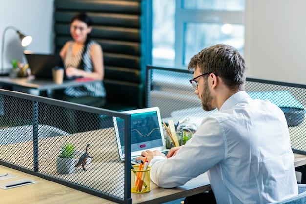 Глубоко в мыслях. сосредоточенный бородатый мужчина смотрит на компьютер и анализирует график