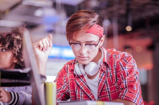 Глубоко в мыслях. довольный подросток сидит за столом во время подготовки к обследованию