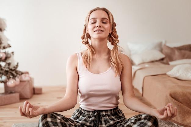 心の奥深く。彼女の寝室の床で瞑想し、長い一日の準備をしている白いシャツを着た静かな女性の笑顔