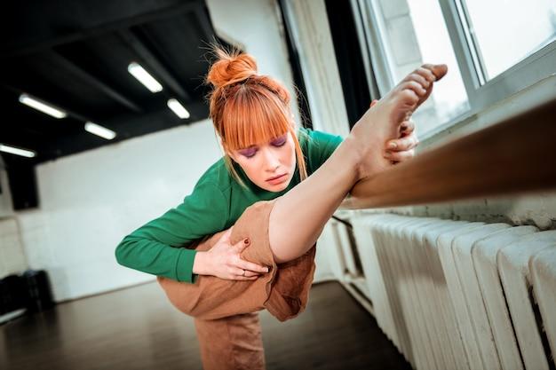 Глубокий наклон. молодой профессиональный артист балета с пучком волос делает глубокий наклон, стоя возле балетной стойки