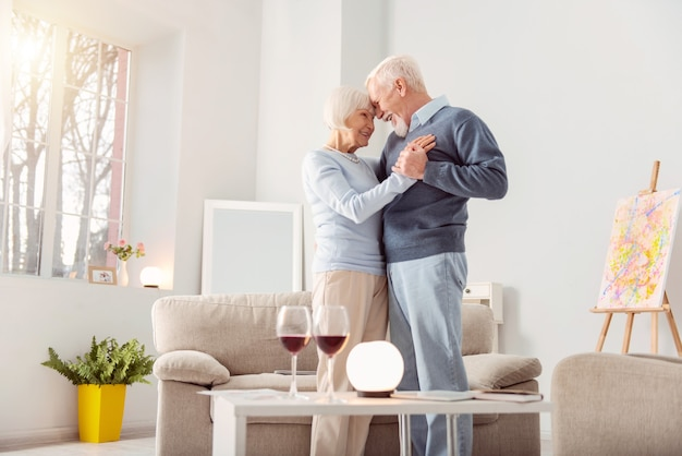Deep in love. pleasant elderly couple dancing waltz in the living room and leaning their foreheads against one another while smiling at each other