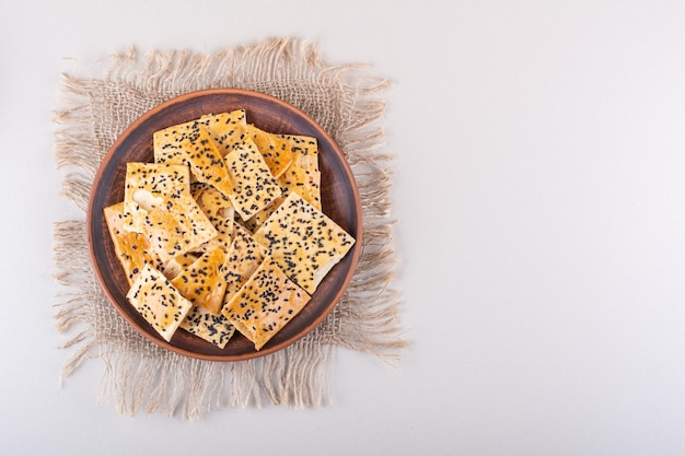 Piatto profondo di cracker con semi neri su sfondo bianco. foto di alta qualità
