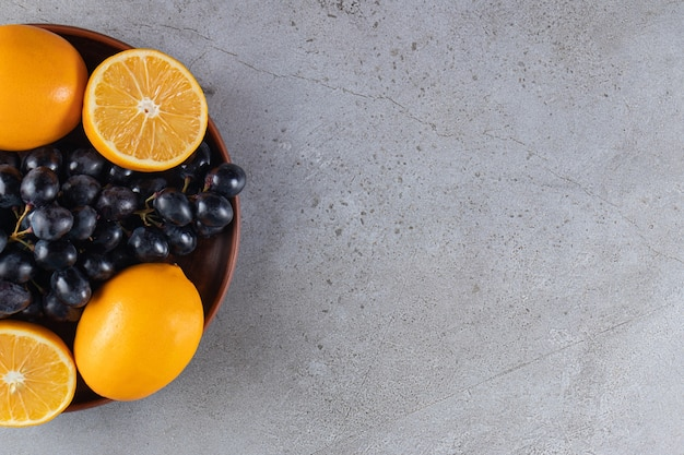 Deep plate of fresh black grapes and oranges on stone table.