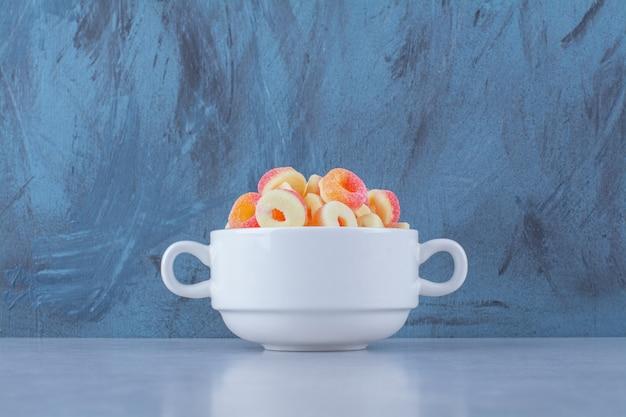 Un piatto fondo pieno di marmellate zuccherate di frutta colorata.