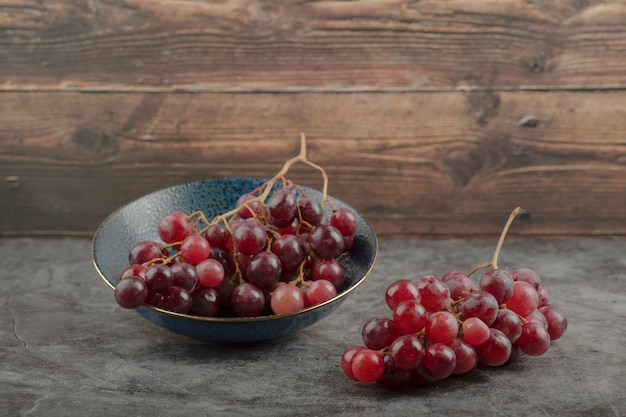 Deep plate of red ripe grapes on marble table.