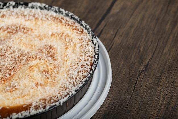 木の表面においしいココナッツパイが入った深皿