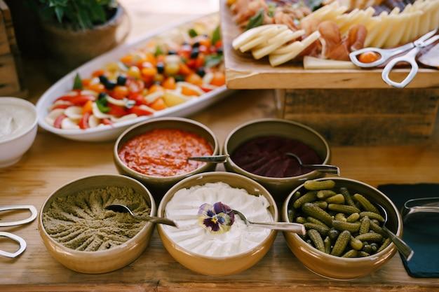 Глубокие тарелки печеночного паштета, десертных солений и томатной пасты на столе с капрезе и сыром и