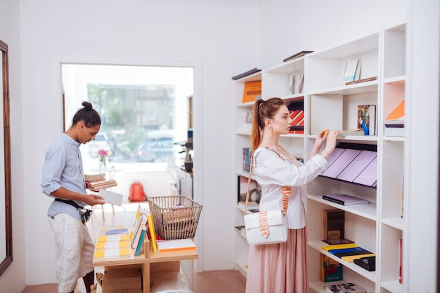 Deep reading. cute female person standing near bookshelves while looking for present
