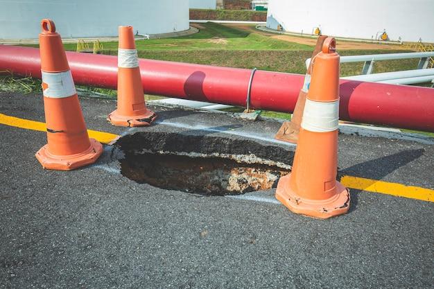 Глубокая воронка на улице города и оранжевый дорожный конус. опасная яма на асфальтовой трассе. дорога с трещинами. плохая конструкция. поврежденный асфальт обрушился и упал