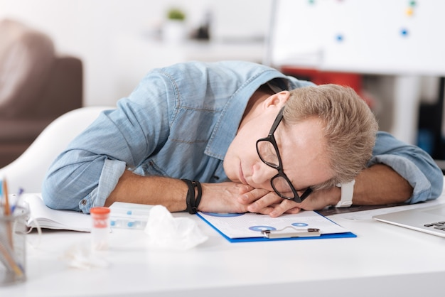 Deep sleep. sick man wearing jeans shirt having glasses on the nose, keeping both hands on the table