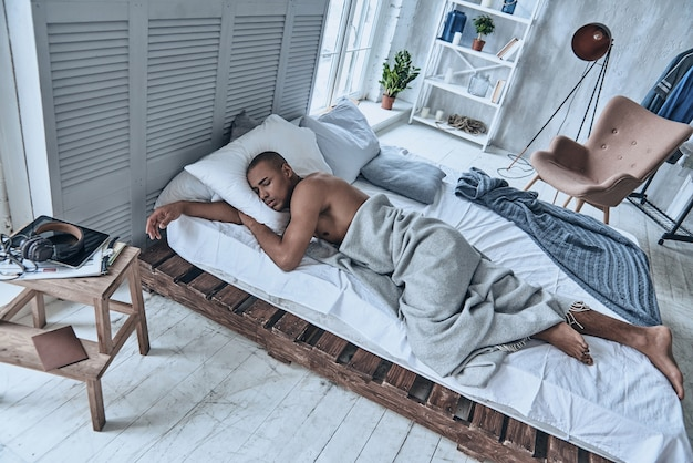 깊은 잠. 집에서 침대에 누워있는 동안 잠자는 젊은 아프리카 남자의 상위 뷰