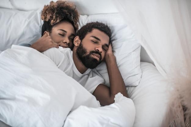 깊은 잠. 침대에서 집에서 푹 자고 수염 난 남자를 껴안고있는 젊은 어두운 피부 예쁜 여자