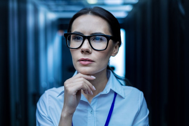 Глубокое мышление. молодая успешная женщина думает и держится за подбородок и смотрит
