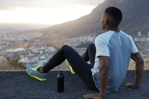 Deep in thoughts black man wears casual sportswear, feels relaxed at top, poses back in front of mountain scenic view, keeps hands on asphalt, has outdoor workout, being fatigue and lack of strength