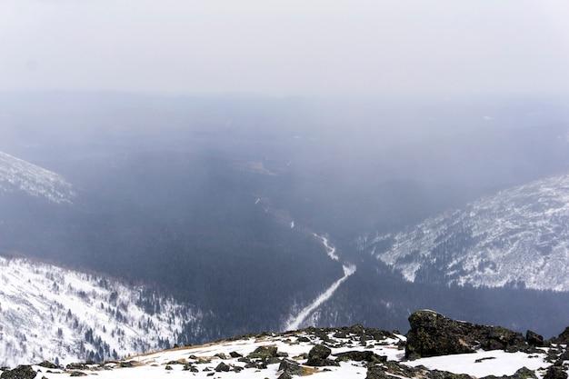 Глубокое лесное ущелье в горах северного урала во время сильного снегопада