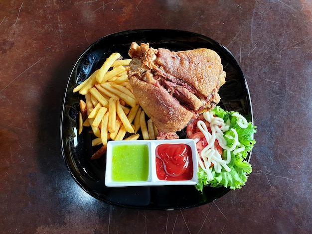 Deepfried german pork knuckle recipe with french fries salad and sauce on wooden background