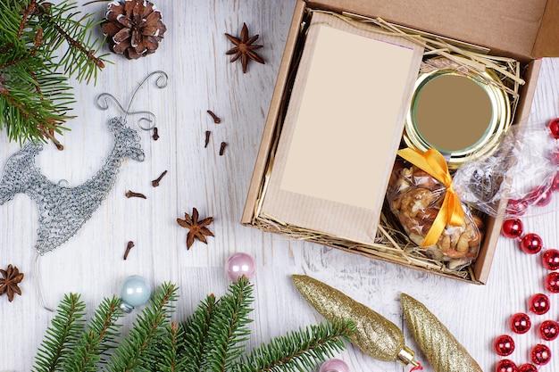 明るい背景にモミの枝とレイアウトの鹿とビーズのクリスマスプレゼント。