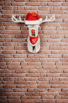Олень висит на стене с шапкой санта-клауса и красным ожерельем. рождественские украшения