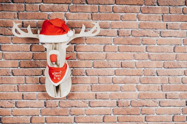 Олень, висящий на стене в шляпе санта-клауса и красном ожерелье. рождественские украшения