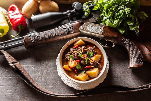 Тушеное мясо оленя в чаше для охотничьего оружия как украшение.