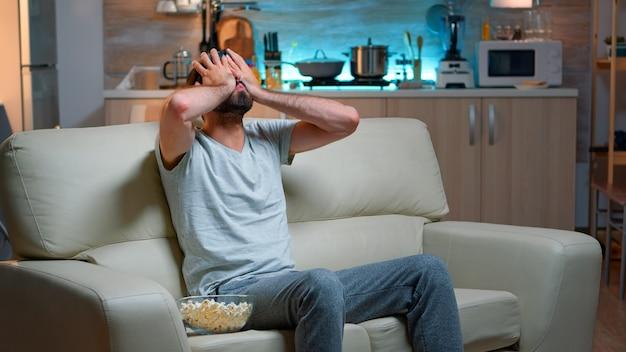 オンライン競争中にテレビでゲームをしている男を倒す