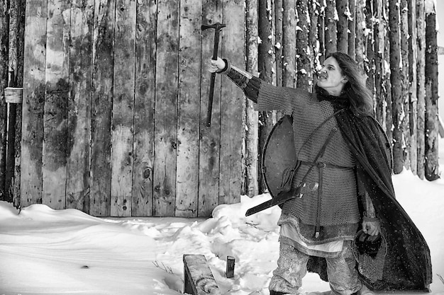 Защитник молодой воин в кольчужных доспехах, вооруженный мечом и топором