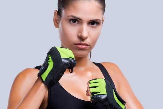 身を守る。灰色の背景に対してポーズをとってスポーツ手袋の魅力的な若いスポーティな女性