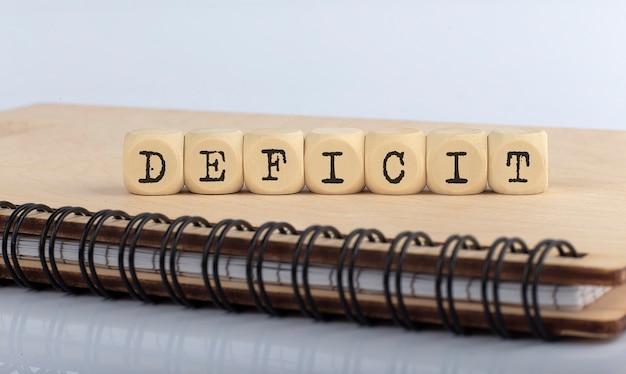 Слово дефицита написано на деревянном блоке на деревянном ноутбуке. концепция вид сверху.