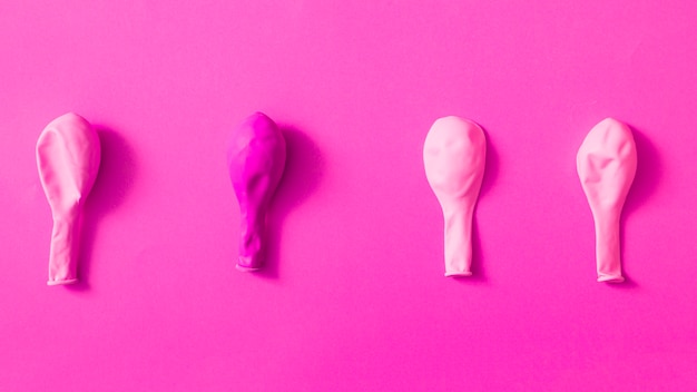 Deflated pink balloons over colored background