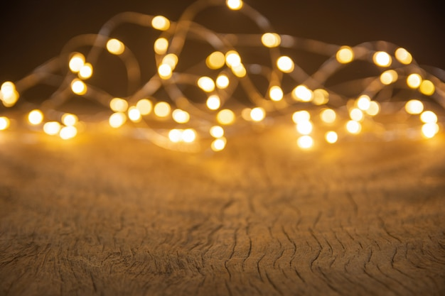 Defocus christmas lights on wooden background. selective focus on wood planks