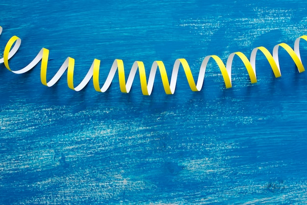 Defocus is a detailed image of colorful streamers serpentine on a wooden blue vintage