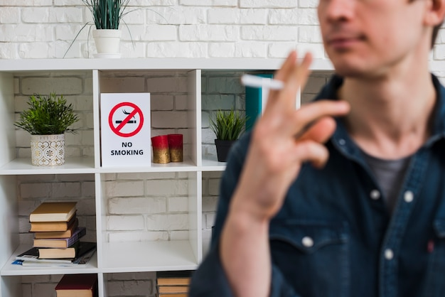 棚の上の禁煙ポスターの前にタバコを持つ男の焦点をぼかします