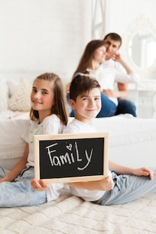 Defocus of romantic couple behind the sibling holding slate with family text
