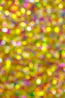 休日のお祝いの間に明るくきらめくぼやけた鮮やかなお祝いの金色の光の焦点がぼけた背景