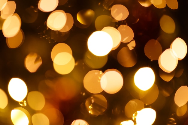 クリスマスの花輪の点滅ライトで焦点がぼけた背景