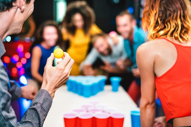 Defocused background of young friends playing beer pong at youth hostel - free time travel concept with backpackers having genuine fun at guesthouse - blurred view of happy people on playful attitude