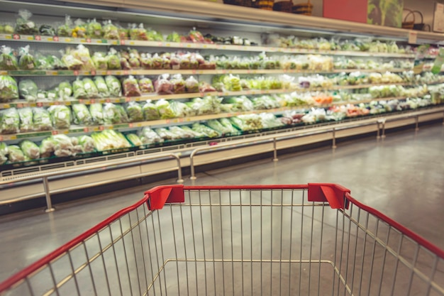 Defocused 흐림 슈퍼마켓에서 바닥 야채 음식에 쇼핑 쇼핑 카트를 구입